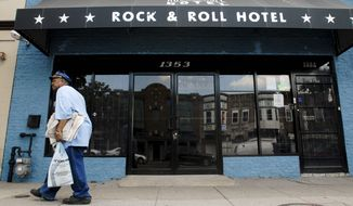 In this Aug. 17, 2006, file photo, Glen Brown, 65, from D.C., passes by the Rock & Roll Hotel, a formal funeral home that was transformed into a bar and concert venue as part of a redevelopment of H street. (Nancy Pastor/The Washington Times )