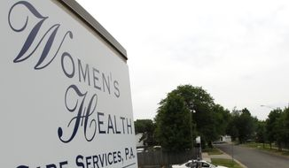 "In this Tuesday, June 2, 2009 file photo, John Pride, of Wichita, Kan., walks past a memorial outside Women's Health Care Services in Wichita, Kan. The family of slain abortion provider George Tiller said Tuesday, June 9, 2009 that Tiller's Wichita clinic will be ""permanently closed."" (AP Photo/Charlie Riedel, file)"