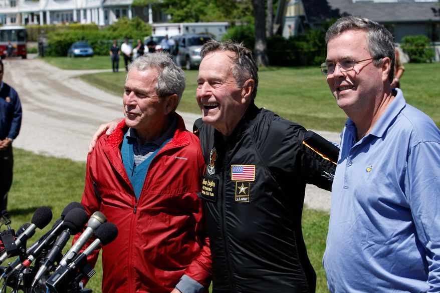 **FILE** Former President George H.W. Bush (center) is joined by his sons, former President George W. Bush and former Florida Gov. Jeb Bush, as he recounts Friday's birthday jump with the Army Golden Knights parachute team to celebrate his 85th birthday. (Associated Press)