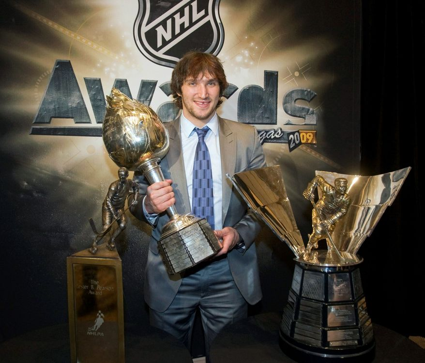 ASSOCIATED PRESS/CANADIAN PRESS ALEXANDER THE GREAT: Washington Capitals star Alex Ovechkin holds the Hart Memorial Trophy as he poses with the Lester B. Pearson Award (left) and the Maurice Richard Trophy.