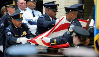 DC Metropolitan Police Honor guard fold the flag draped over the casket of Stephen T. Johns following his funeral service. The funeral for 39-year-old Johns, the security guard who was shot and killed at the U.S. Holocaust Memorial Museum, was held at Ebenezer AME Church in Fort Washington, Md., on Friday beginning with a viewing at 9 a.m. and funeral service at 11 a.m. Friday, June 19, 2009 ( Mary F. Calvert / The Washington Times )