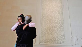 DAD'S DAY: Imbundu Charles W. Namasaka and daughter Nyjai, 8, of Upper Marlboro, visit the Lincoln Memorial on Saturday while attending the National Rally for Responsible Fatherhood event in Washington. (Mary F. Calvert/The Washington Times)