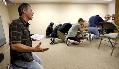 Troy Newman, left, president of Operation Rescue, prays during a memorial for abortion deaths at Operation Rescue's headquarters Saturday, June 20, 2009, in Wichita, Kan. (AP Photo/Charlie Riedel) ** FILE **