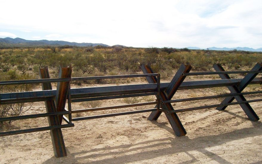 This Normandy-style barrier fence along the U.S.-Mexico border near Columbus, N.M., features extra low and high bars to prevent livestock from crossing and possibly spreading disease. (Associated Press)