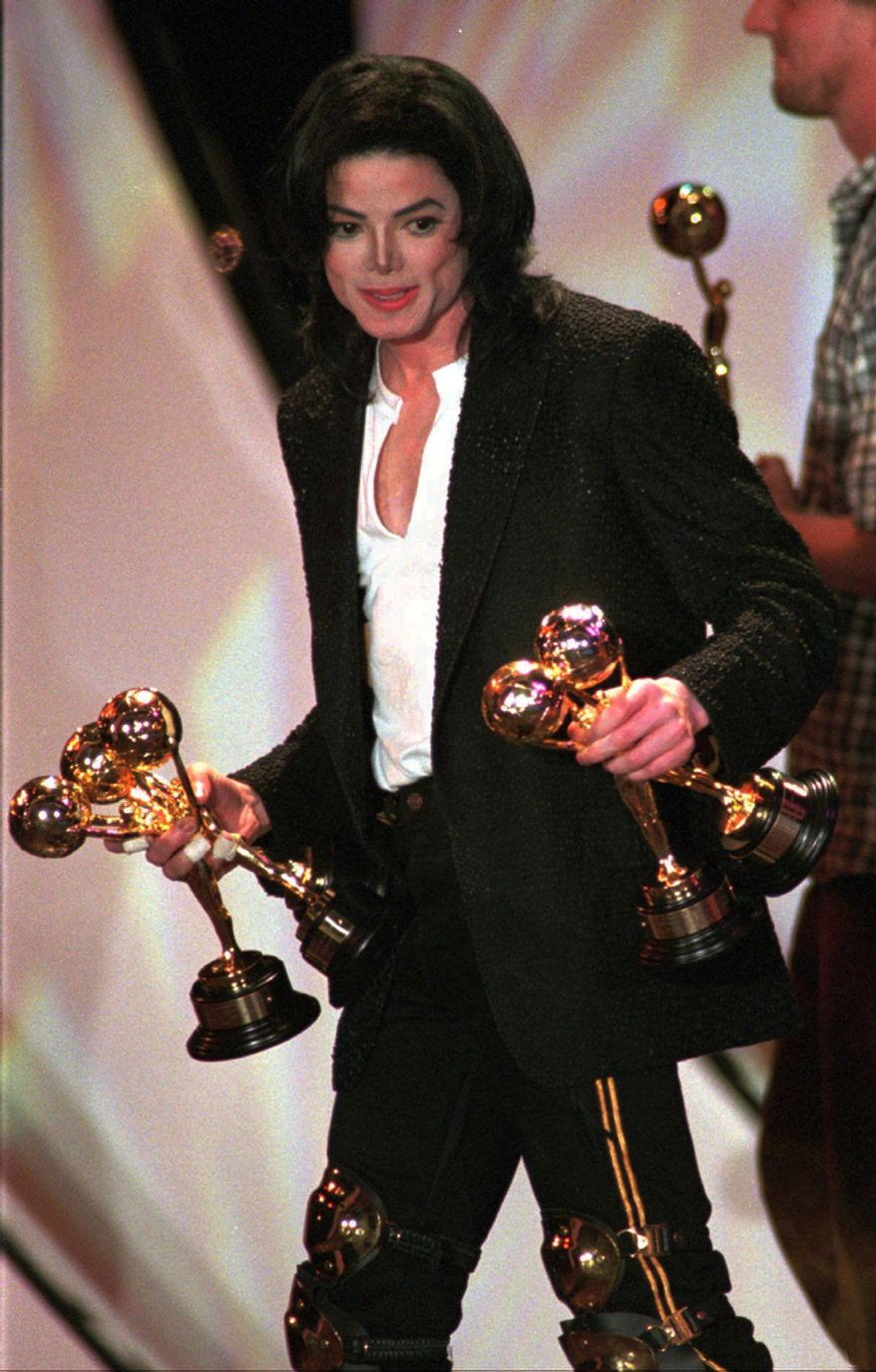 **FILE** Michael Jackson leaves the stage of the Monte Carlo Sporting Club after receiving his fifth trophy during the World Music Awards on May 8, 1996. (Associated Press)