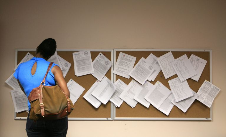 Janet Francis looks at job postings at the New York State Department of Labor on Thursday in the Brooklyn section of New York. Francis, 36, of Brooklyn, has been unemployed for two years and has used the time to work toward her college degree in social work.