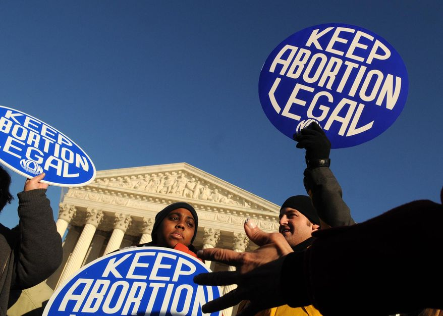 **FILE** Lisa King (left) and Gus Turner hold pro-choice signs in front of the Supreme Court Building in 2009 while debating with pro-life protesters at the annual March for Life rally. (The Washington Times)