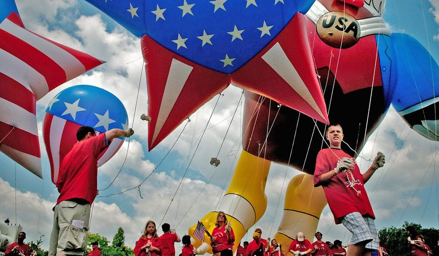 A family from Long Island, N.Y., holds onto a flag-themed balloon as the foursome prepares to march in the National Independence Day Parade on Constitution Avenue in Northwest Saturday. (Allison Shelley/Washington Times/File)
