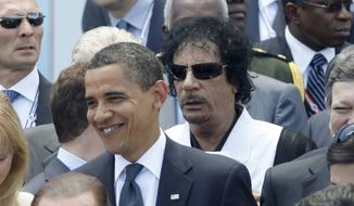 President Barack Obama, left, is followed by Libyan leader Moammar Gadhafi before a group photo at the G-8 Summit in L'Aquila, Italy, Friday, July 10, 2009. (AP Photo/Charles Dharapak)