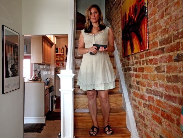 **FILE** Federal employee Lynda Salvatore holds her Glock 21 handgun in her home in the Columbia Heights neighborhood, where she says she feels safer since the Supreme Court overturned the District's ban on gun ownership. (The Washington Times)