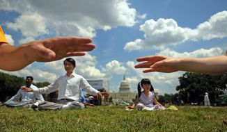 Joel Ng, 5, joins her dad, Ulane Eng (second from left), for meditation Sunday on the Mall as Falun Gong practitioners and their supporters mark the 10th anniversary of a Chinese crackdown on the spiritual movement. It has gained millions of followers since its 1992. founding. (By Astrid Riecken/The Washington Times/File)