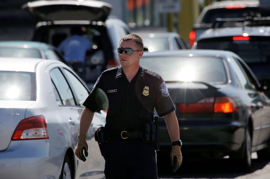 Associated Press A U.S. Customs and Border Protection officer walks through a line of cars at a crossing from Blaine, Wash. With more illegal drugs being smuggled across the U.S.-Canada border, the United States is beefing up its presence in the north.