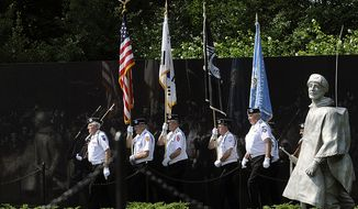 ** FILE ** An honorary color guard made of up members of the Korean War Veterans Association marches into the Korean War Veterans Memorial in Washington on Monday, July 27, 2009, for a wreath-laying following a ceremony commemorating the cease-fire that took place in Korea on July 27, 1953, as well as those who served in the conflict. (The Washington Times)
