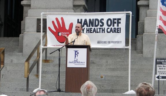"""In this file photo, Jon Caldara, president of the Independence Institute, fires up the crowd at Colorado's Capitol in Denver during a 2009 rally condemning President Obama's proposed health care plan. Mr. Caldara was recently let go from the Denver Post, where he had a regular opinion column. He says the liberal editor who terminated him did so because of his views on transgender rights issues being """"insensitive."""" (Valerie Richardson/The Washington Times) **FILE**"""
