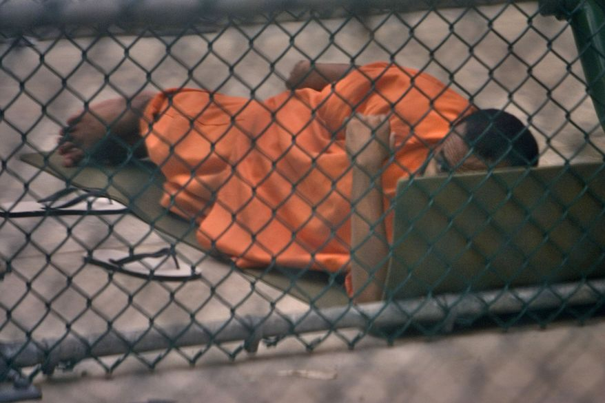 ** FILE ** In this Nov. 19, 2008, photo reviewed by the U.S. military, a Guantanamo detainee glances up while resting on a foam pad inside a fenced-in outdoor exercise area at the Camp 6 high-security detention facility on the U.S. naval base at Guantanamo Bay, Cuba. (AP Photo/Brennan Linsley)
