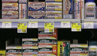 Packages of aspirin fill the shelves of a drugstore, Tuesday, Aug. 11, 2009 in Chicago. A study suggests colon cancer patients who took aspirin reduced their risk of death from the disease by nearly 30 percent. (AP Photo/M. Spencer Green)
