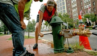 Above: Casey Trees' bicycle Crew Captain Karja Hansen turns on a Massachusetts Avenue fire hydrant, the water source the crew uses to water trees, as intern Evan Douglas looks on. Casey Trees has the nation's first bike-powered program to care for trees. Intern Heydi Lovo (right and below right) waters her trees.