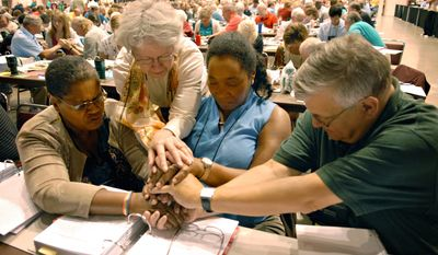 ** FILE ** Evangelical Lutheran Church in America voting members (from left) Orinda Hawkins-Brinkley, Diane Yeager, Marj Ellis and Steven Schnittke, along with others, pray during the church's General Assembly in Minneapolis in 2009, at which the denomination approved resolutions in support of gays.