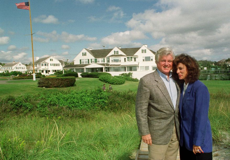 ** FILE ** Sen. Edward M. Kennedy, D-Mass., left, stands with his wife Victoria Reggie Kennedy in front of houses inside the Kennedy compound in Hyannis Port, Mass., in this Sept. 13, 1992, file photo. He died in 2009. (AP Photo/Susan Walsh)
