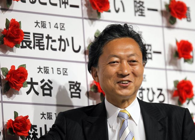 Yukio Hatoyama, leader of the Democratic Party of Japan, the country's main opposition party, smiles surrounded by red rosettes attached on victorious candidates' names during the ballot counting for the parliamentary elections at the party's election center in Tokyo on Sunday, Aug. 30, 2009. The DPJ was set to win more than 300 of the 480 seats in the lower house of parliament, ousting the Liberal Democrats, who have governed Japan for all but 11 months since 1955, according to projections by all major Japanese TV networks. (AP Photo/Itsuo Inouye)