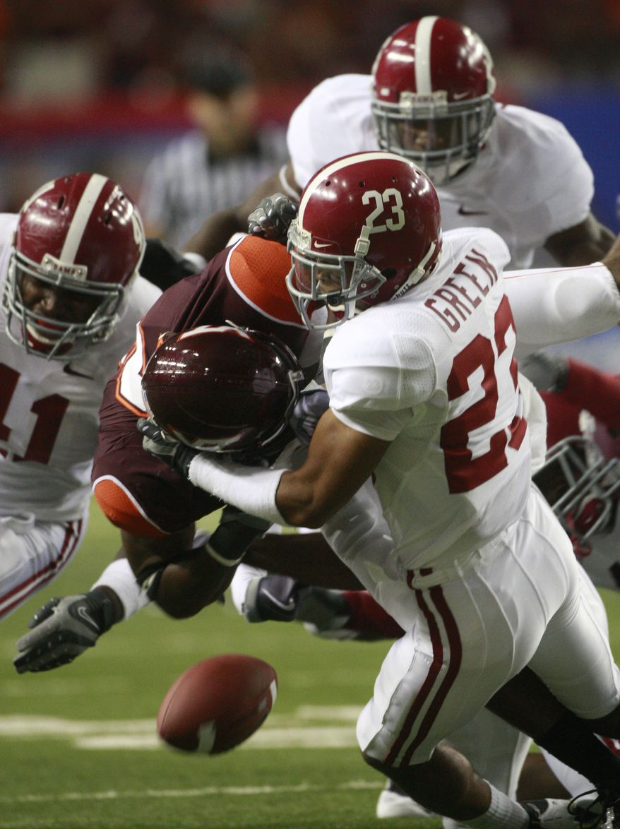 ** FILE ** Alabama's Robby Green (23) knocks the ball away from Virginia Tech's Davon Morgan (2) during their NCAA college football game at the Georgia Dome in Atlanta Saturday, Sept. 5, 2009.The Atlantic Coast Conference, of which Virginia Tech is a member, has had anything but a lazy summer, thanks to realignment rumors, NCAA investigations and other incidents. (AP Photo/Dave Martin)