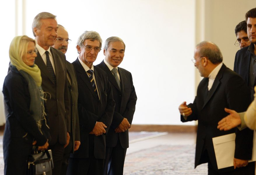 **FILE** Iranian Foreign Minister Manouchehr Mottaki (right) welcomes diplomats representing the five permanent members of the U.N. Security Council and Germany (left) prior to presenting Iran's package of proposals for new talks with the West in a gathering in Tehran, Iran. (Associated Press)