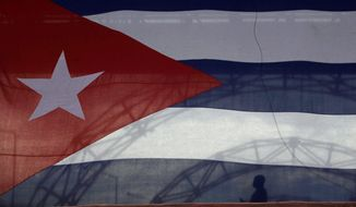 A man silhouetted by a Cuban flag marks a moment of silence Saturday for Cuban Vice President Juan Almeida Bosque, who died Friday at 82. (Associated Press/file) ** FILE **