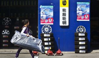 **FILE** A woman with car accessories passes by a tire store in Beijing, China, on Sept. 13, 2009. (Associated Press)