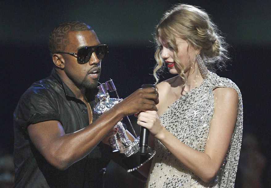 ** FILE ** Singer Kanye West (left) takes the microphone from country singer Taylor Swift as she accepts the Best Female Video award during the MTV Video Music Awards on Sunday, Sept. 13, 2009, in New York. (AP Photo/Jason DeCrow)