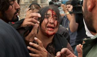 An Afghan woman injured in a Taliban bombing cries for help near the site where a suicide bomber attacked an Italian military convoy on a road in Kabul in this September 2009 photo. (Associated Press)