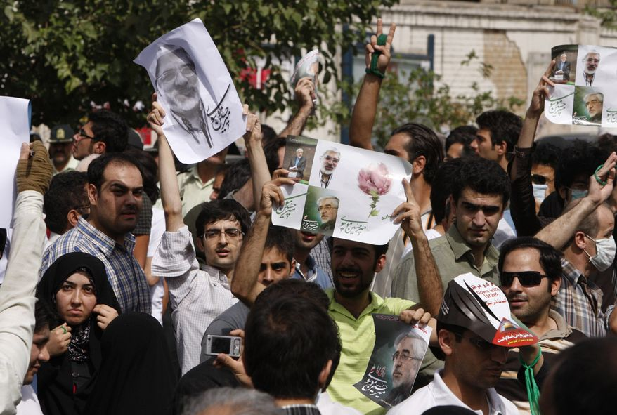 Iranian opposition supporters attend a protest, as they hold pictures of opposition leader Mir Hossein Mousavi, in Tehran, Iran, Friday, Sept. 18, 2009. Thousands of opposition supporters held protests in competition with government-sponsored mass rallies to mark an annual anti-Israel commemoration, the Quds Day that reflects the Persian nation's sympathy with the Palestinians. (AP Photo/Vahid Salemi)
