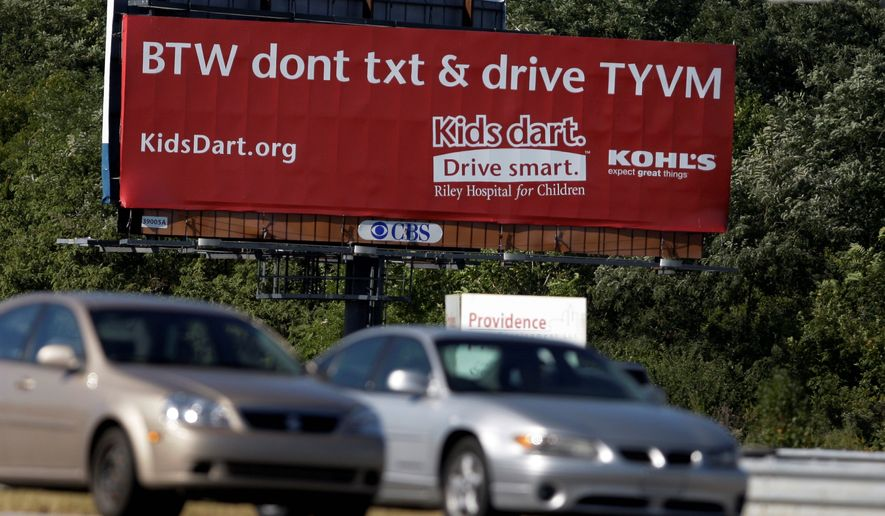 Motorists pass a billboard encouraging people not to text while driving in Indianapolis, where drivers younger than 18 are banned from using cell phones. (Associated Press)