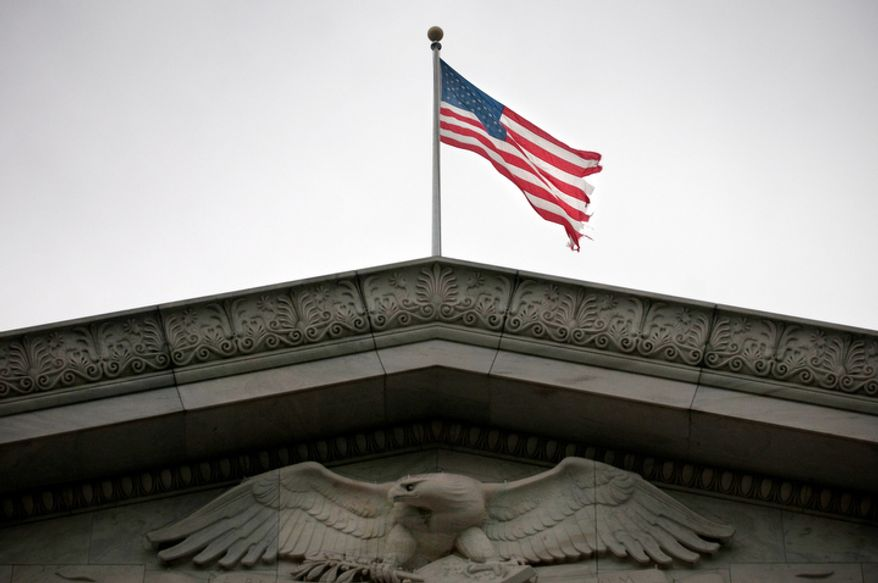 ** FILE ** A tattered flag flies over the Rayburn House Office Building on Capitol Hill in Washington in 2009. (The Washington Times)