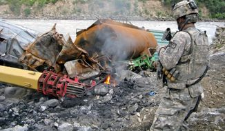 PHOTOGRAPHS BY RICHARD TOMKINS/THE WASHINGTON TIMES A soldier looks over the wreckage of a supply convoy Taliban insurgents attacked in Afghanistan's Kunar province. The province is a main infiltration route for Taliban insurgents heading to and from Afghanistan's central regions.