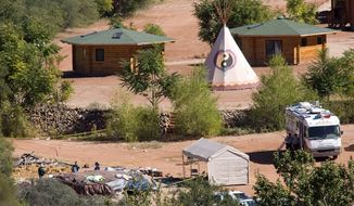 ** FILE ** Investigators examine a sweat lodge at the Angel Valley Retreat Center near Sedona, Ariz., where two people died in October 2009 after being overcome during a spiritual retreat. (AP Photo)