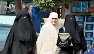 Egyptian students wearing the face-covering veil known as the niqab walk with another wearing a khemar-style hijab last week in Cairo. (Associated Press) ** FILE **