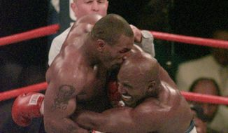 """Mike Tyson and Evander Holyfield, seen here in the 1997 match when Mr. Tyson bit off part of Mr. Holyfield's ear, will meet Friday on """"The Oprah Winfrey Show."""" **FILE**"""