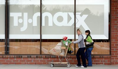 """A shopper pushes her purchases and a child outside a T.J. Maxx clothing store in Braintree, Mass. TJX, the parent company of both Marshalls and T.J. Maxx, is hoping to take advantage of so-called """"frugal fatigue."""""""