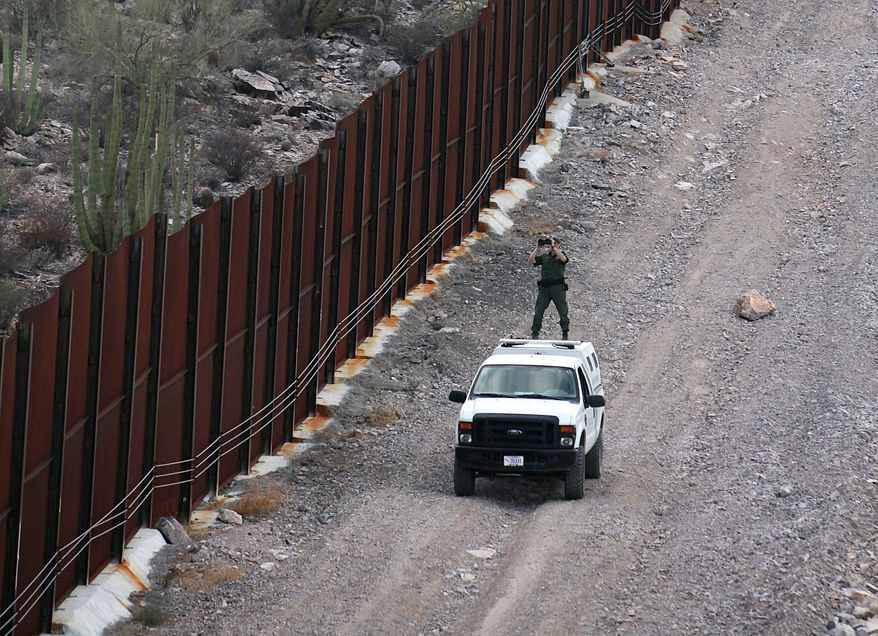 ** FILE ** A U.S. Border Patrol agent checks the border with Mexico near the Lukeville port of entry in Arizona in 2009. Organ Pipe Cactus National Monument lies on both sides of the small border town of Lukeville. An organ pipe cactus can be seen on the Mexican side of the border. (Lindsay A. Miller)