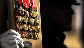 A Marine holds up posthumous medals of honor to be presented to the family of a fallen soldier during the Remembering the Brave Ceremony at the National Museum of the Marine Corps in Triangle, Va., Friday, October 23, 2009. (Peter Lockley / The Washington Times)