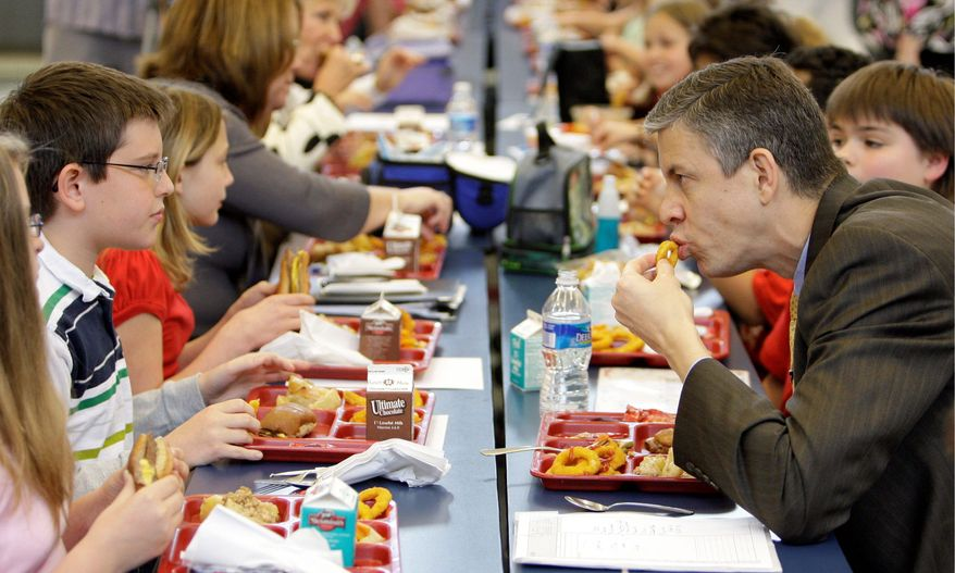 ** FILE ** Education Secretary Arne Duncan (right) has lunch with students at Eagle School in Martinsburg, W.Va., in 2009. First lady Michelle Obama and Agriculture Secretary Tom Vilsack are expected to announce Wednesday, Jan. 25, 2012, that most school meals will have less sodium, more whole grains and more fruits and vegetables. (Associated Press)
