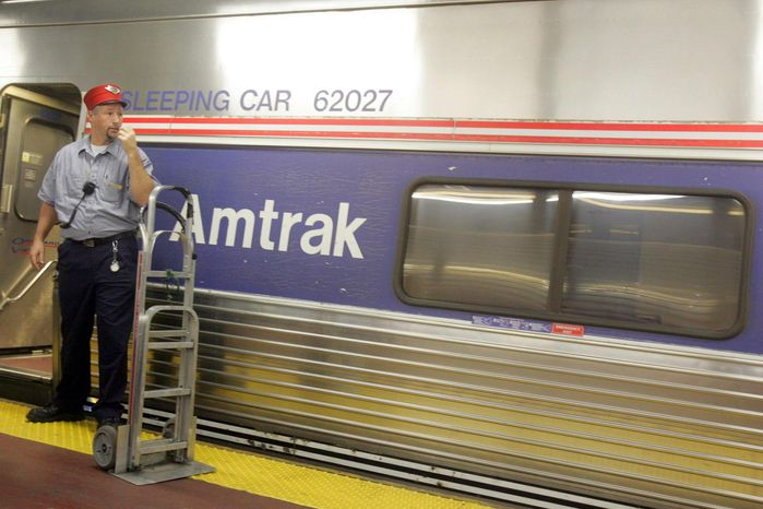 **FILE** A Red Cap stands next to an Amtrak train waiting for passengers at a platform at New York's Penn Station in 2005. (Associated Press)