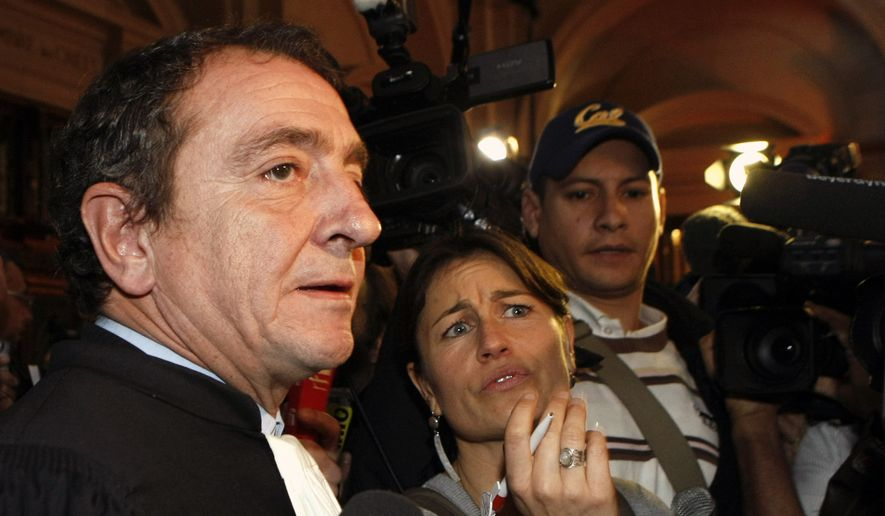 Church of Scientology lawyer Patrick Maisonneuve, left, speaks to reporters after a court returned a verdict of fraud against the group, at a Paris courthouse on Tuesday, Oct. 27, 2009. (AP Photo/Jacques Brinon)