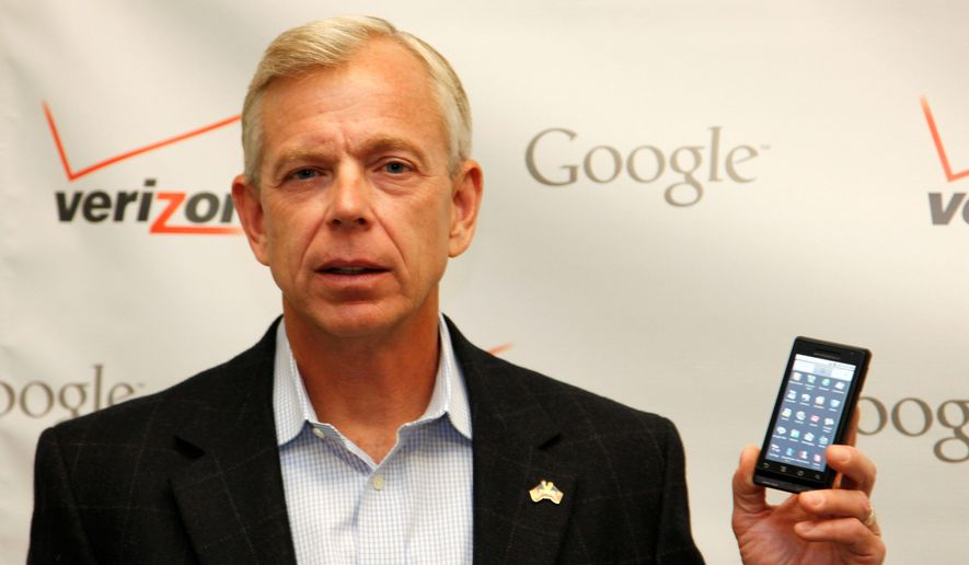 Lowell McAdam, president and CEO of Verizon Wireless, shows off a Motorola cell phone containing Google's Android software during a joint announcement with Google in New York. (Associated Press) ** FILE **