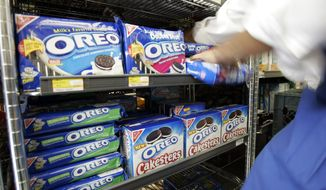 FILE - A worker fixes the display of Kraft Food's Oreo cookies at a Market in Palo Alto, Calif., in this file photo dated Monday, July 28, 2008. Shares in British chocolate maker Cadbury PLC edged higher on Monday Nov. 9, 2009, as a deadline loomed for Kraft Foods Inc. to make a formal takeover offer for the candy maker, or under British takeover rules Kraft will be prohibited from making a new offer for six months. Cadbury has already spurned a $16.7 billion cash-and-stock offer from Kraft. (AP Photo/Paul Sakuma, FILE)