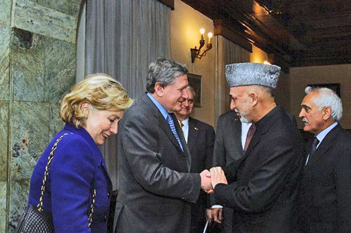 ** FILE ** Secretary of State Hillary Rodham Clinton (left) looks on as Afghan President Hamid Karzai (second from right) greets Richard C. Holbrooke, the U.S. special representative for Afghanistan and Pakistan, at the Presidential Palace in Kabul, Afghanistan, on Wednesday, Nov. 18, 2009. (AP Photo/U.S. Embassy)