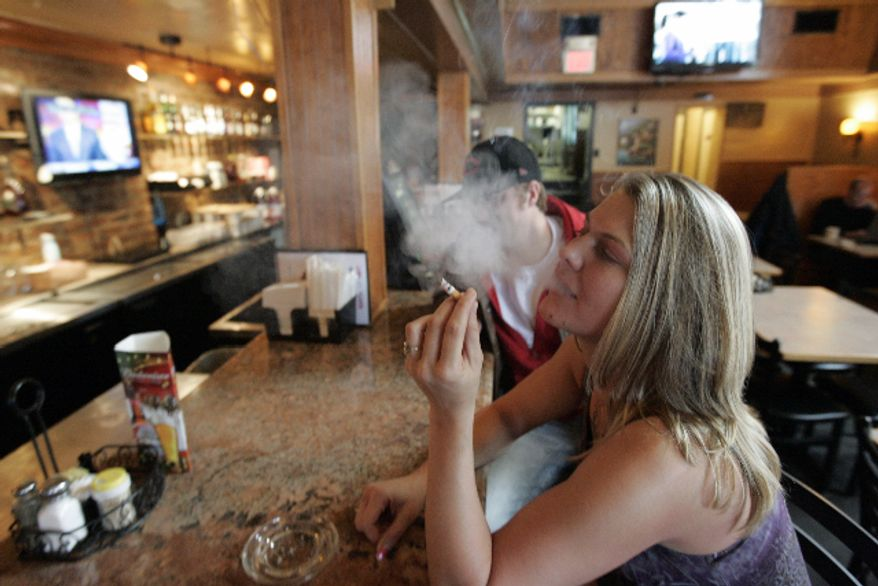 ** FILE ** Third Street Diner employee Jessica Prignano takes a smoke break at the bar in the diner in Richmond in November 2009. (AP Photo/Steve Helber, File)