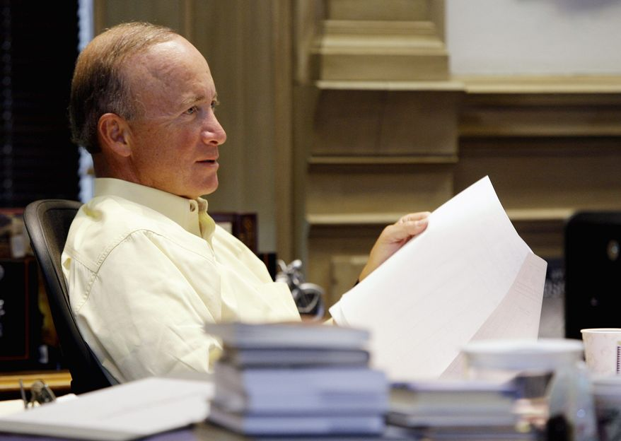 ** FILE ** Indiana Gov. Mitch Daniels meets with his staff in his office at the Statehouse in Indianapolis in November 2009. (AP Photo)