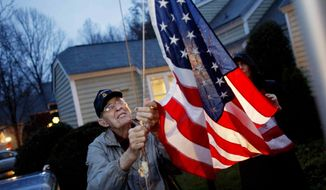 Medal of Honor recipient Col. Van T. Barfoot, 90, lowers the flag outside his home in the Sussex Square subdivision in western Henrico County, Va., on Wednesday, Dec. 2, 2009. According to the subdivision's homeowner association's board, Col. Barfoot is in violation because he flies the flag from a flagpole instead of a pole attached to his porch or doorway. Col. Barfoot has been ordered to remove the pole by 5pm on Friday or face legal action. (AP Photo/Richmond Times-Dispatch, Eva Russo)