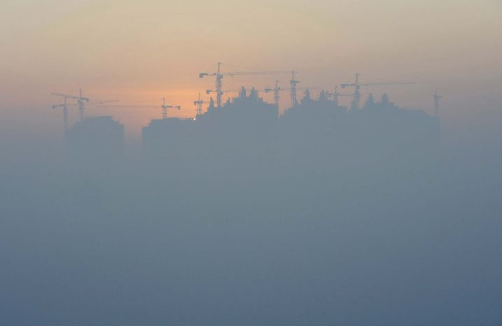 ** FILE ** The sun rises behind the construction site of a housing project among the haze clouding the skyline of Shenyang, China, Sunday, Dec. 6, 2009. (Associated Press)